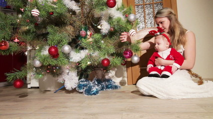 Mother with her baby near Christmas tree