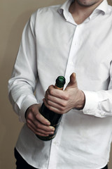 A Waiter in white shirt opens a Bottle of Champagne