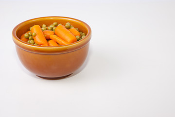 Bowl of boiled carrots and green peas