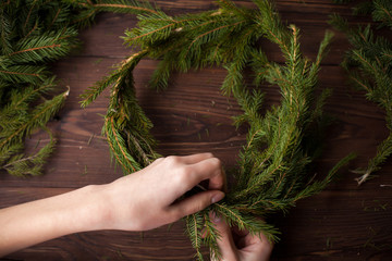 Making Christmas wreath with hands on wooden background