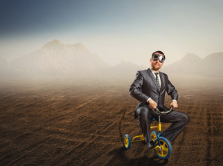 Odd businessman riding a small bicycle
