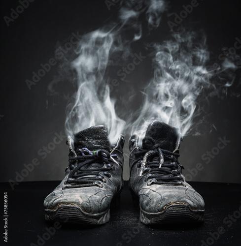 Leinwanddruck Bild Old work shoes in smoke