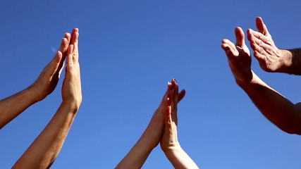 Clapping hands from three persons in front of a blue sky