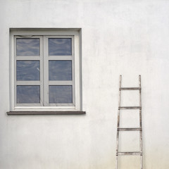 stucco wall with window and wooden ladder
