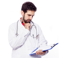 Pensive young doctor looking to the clipboard, isolated on white