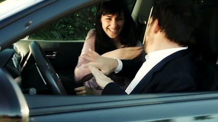 Business couple having fun dancing sitting in car