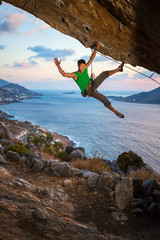 Cheerful rock climber waving his hand while climbing at sunset