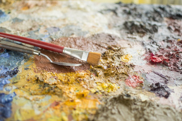 Close up of focused trowel and brush on painting palette