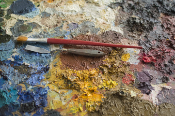 Oil paint on palette with trowel and brush on it