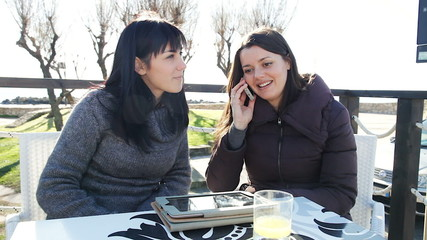 Happy women talking on the phone with man laughing outdoors