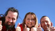 group of adults are holding thumbs up in front of a blue sky