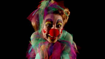 female clown is making grimaces in front of  black background