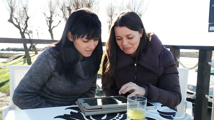 Two beautiful women having fun with tablet outdoors