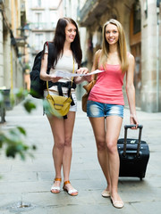 Girls with luggage and map