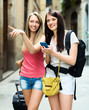 Two smiling girls using  smartphone  for find a way