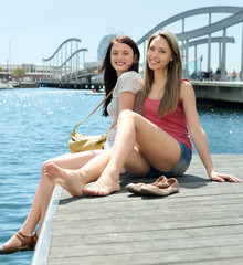 Two happy young girl sitting on the berth