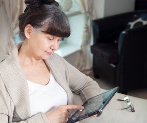 Pension age good looking woman looking internet in tablet device