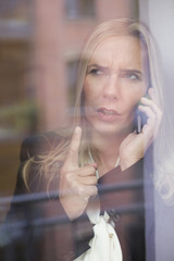 blond woman by the window on the phone