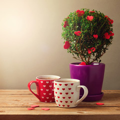 Tree plant with heart shapes and cups of tea for Valentine's day