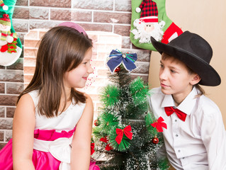 Boy gentleman and girl in ball dress by fireplace.