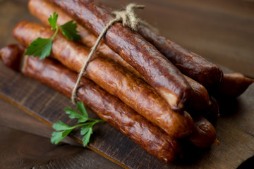 Stack of smoked sausages on a rustic chopping board, close-up