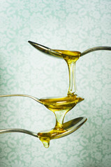 close up of honey dripping from spoons