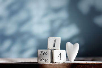 """Three cubes with """" feb. 14 """" words and a white heart ,  backgrou"""