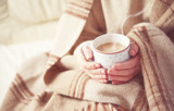 Fototapety cup of hot coffee warming in the hands of a girl