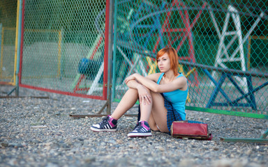 Young red-haired girl in a short skirt sitting at the fence