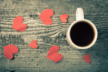 Valentine hearts and cup of tea on the old wooden table. Toned