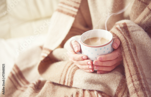 cup of hot coffee warming in the hands of a girl - 75868825