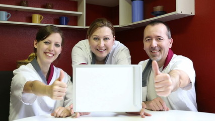 three doctors showing clipboard and lifting thumbs up