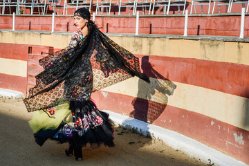 Woman, model of fashion, wearing a dress in a bullring