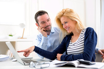 Young attractive couple using laptop at home