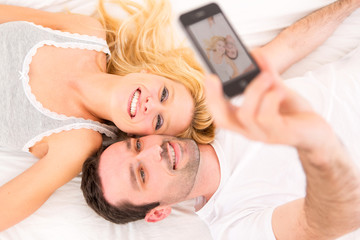 Young attracttive couple taking selfies in bed