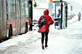 Commuter running to bus in snowstorm