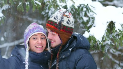 Happy young couple having fun in a winter forest.