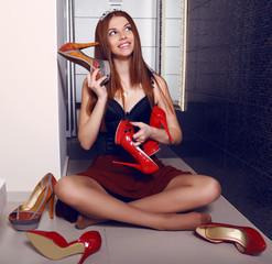beautiful  girl with dark hair posing among shoes in wardrobe