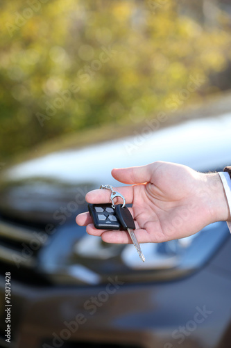 canvas print picture Male hand with car key on car background
