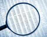 financial data see through lens of loupe on financial newspaper - 75873636