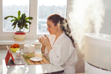 Woman drinking tea reading tablet at humidifier