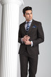 business man posing near white column on grey studio background