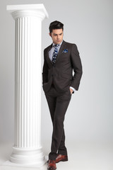 Full length picture of a young business man looking down