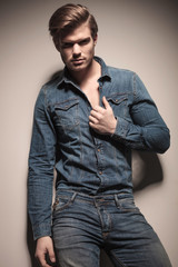 Attractive young fashion man pulling his shirt