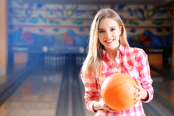 Young woman holding bowling ball in club