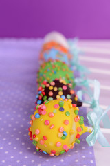 Sweet cake pops on table on purple background