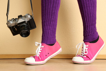 Girl in sneakers with retro photo camera in room