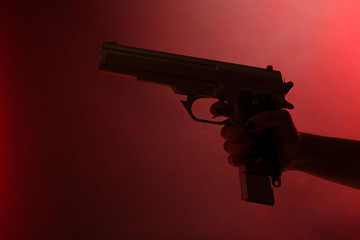 Hand holding gun on red background