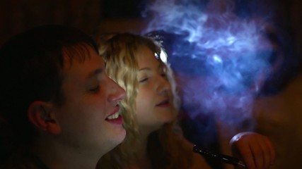 Friends smoke a hookah at a party