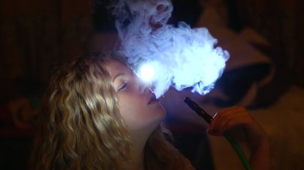 girl smokes a hookah at a party
